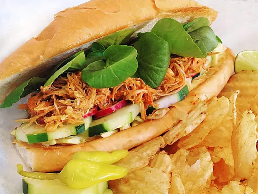 The Pan con Pavo sandwich from gobble This, in Albuquerque, New Mexico. Pulled turkey in a rich Salvadoran mole sauce topped with slaw, cucumber, radish, and fresh watercress, with a side of kettle chips and pickled yellow peppers.