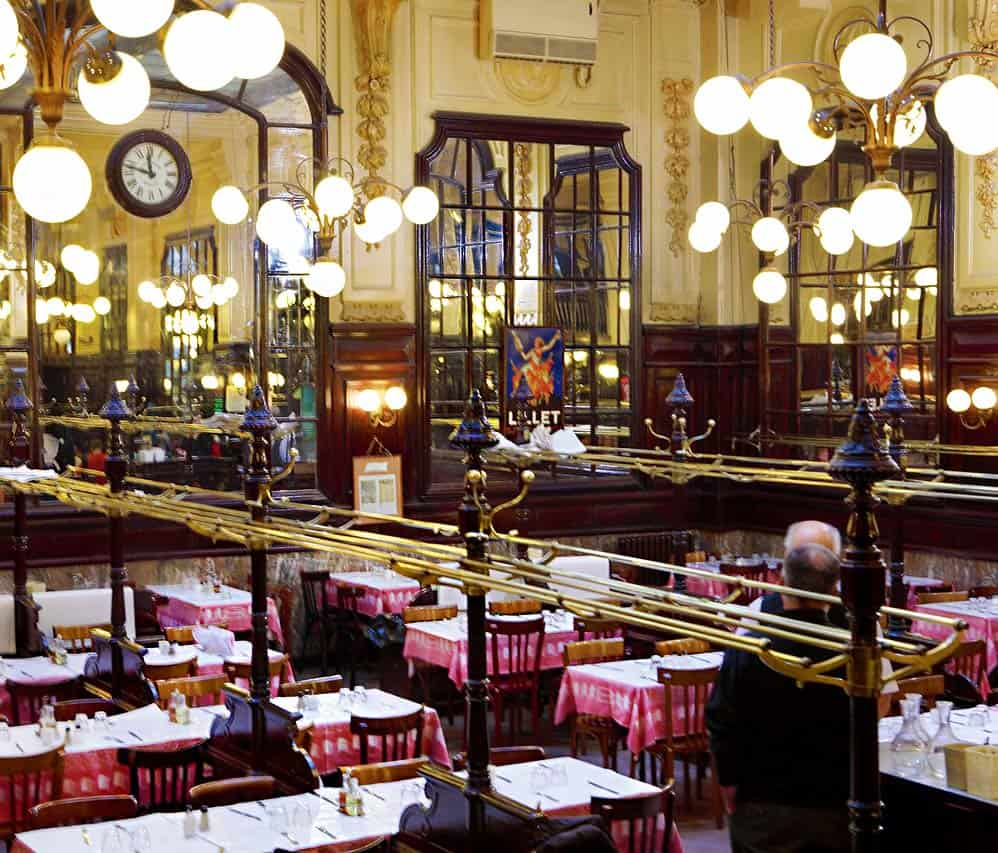 The interior of Restaurant Bouillon Chartier, in Paris, showing its Belle Epoque style, with a high glass ceiling, globe light chandeliers, soaring mirrors and red-and-white tablecloths topped with white paper for writing your order and calculating your bill on.