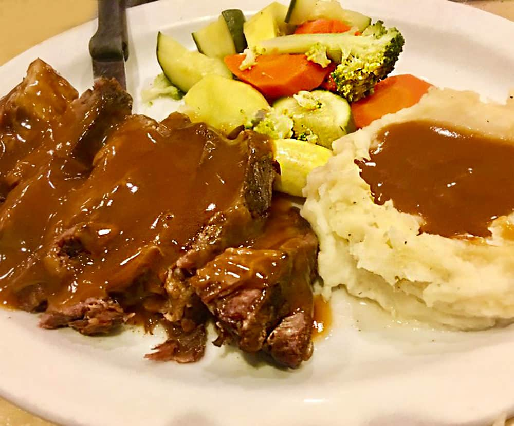 The pot roast at The Lighthouse Cafe & Deli in San Pedro, California, slathered with rich brown gravy and accompanied by mashed potatoes and steamed fresh vegetables