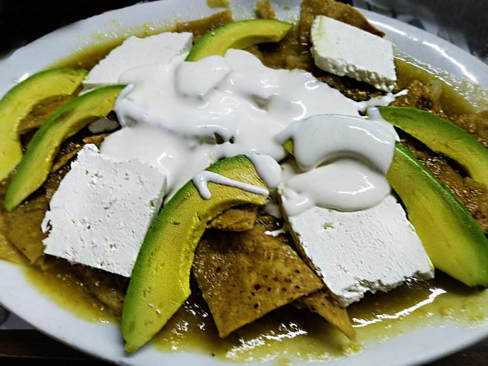 A delicious plate of traditional Mexican chilaquiles, made from crispy tortilla chips topped with fresh farmer's cheese, avocado, salsa verde, and sour cream. Yum!