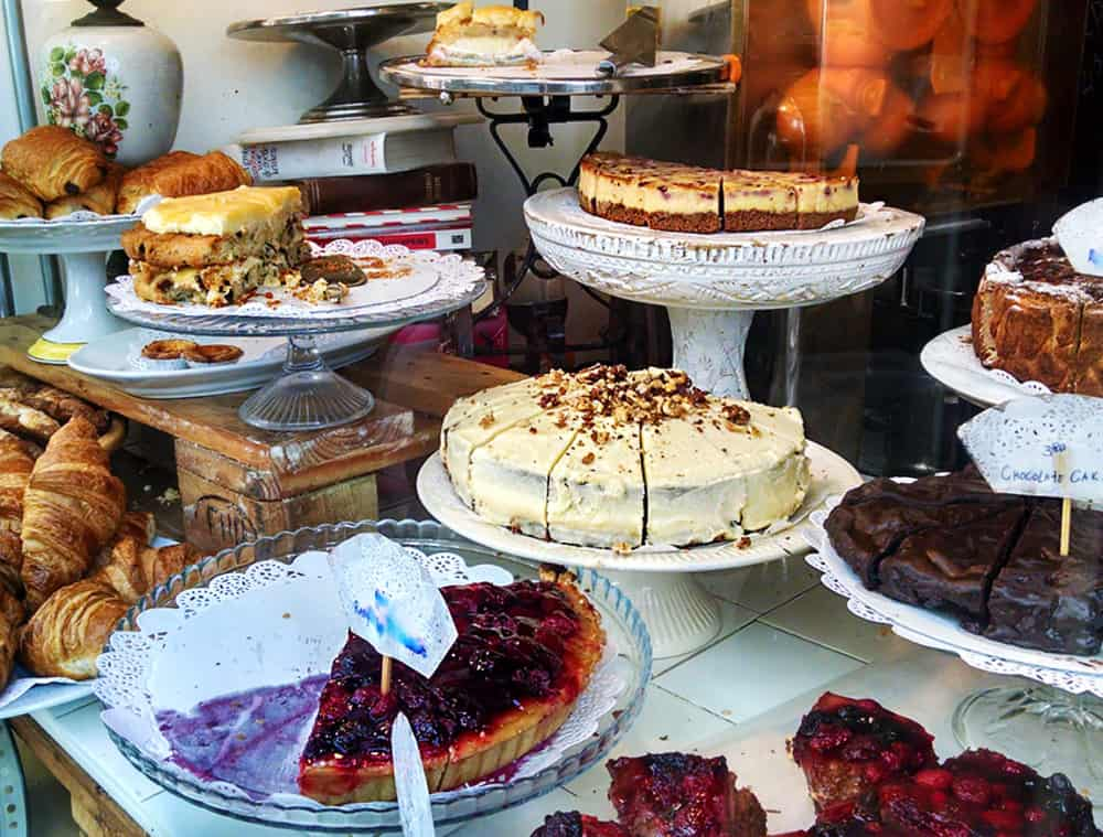 The fron window of De Laatste Kruimel is stacked high with vintage cake plates full of cakes and pies, cheesecake, brownies, and more.