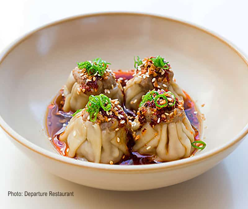 A bowl of pork dumplings in a rich brown sauce from Departure Restaurant, Portland, OR