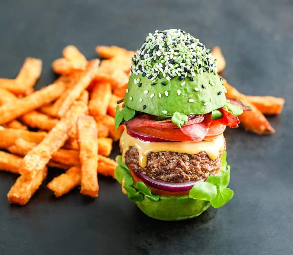 The Bun Burger, from The Avocado Show, replaces the bun with a whole avocado, cut in half crosswise and filled with Angus beef, lettuce, tomato, bacon and cheese.