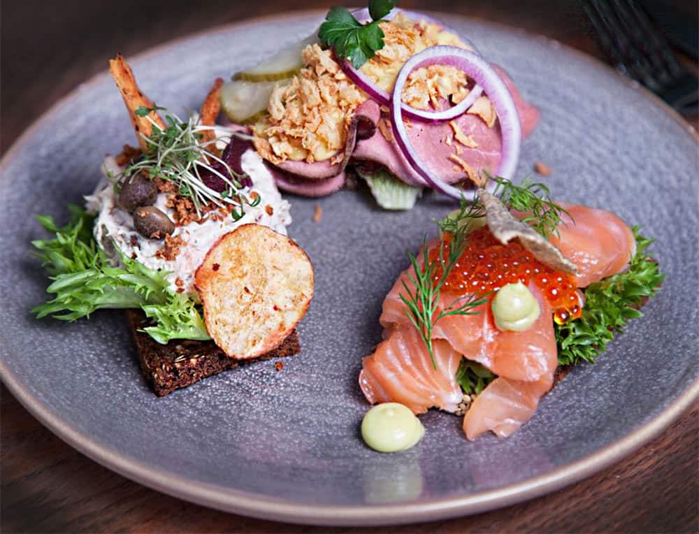 A plate of three Danish smørrebrød from Restaurant Maven in Copenhagen: Icelandic salmon with fennel, beef with horseradish and crisp fried onions, and chicken salad with capers.