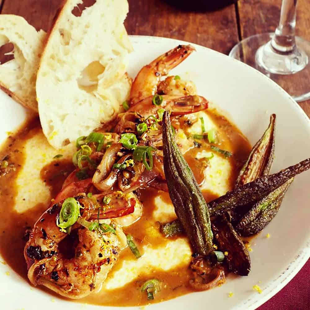A heaping plate of shrimp and grits, with fresh bread and crispy okra, from Over Yonder Restaurant in Valle Crucis, North Carolina.