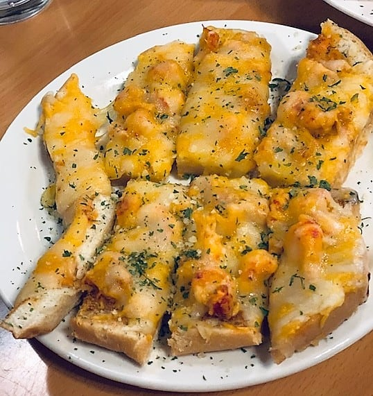 Warm, cheesy bread covered generously with fresh crawfish is a favorite among the appetizers at Luna Bar & Grill in Lake Charles, Louisiana.