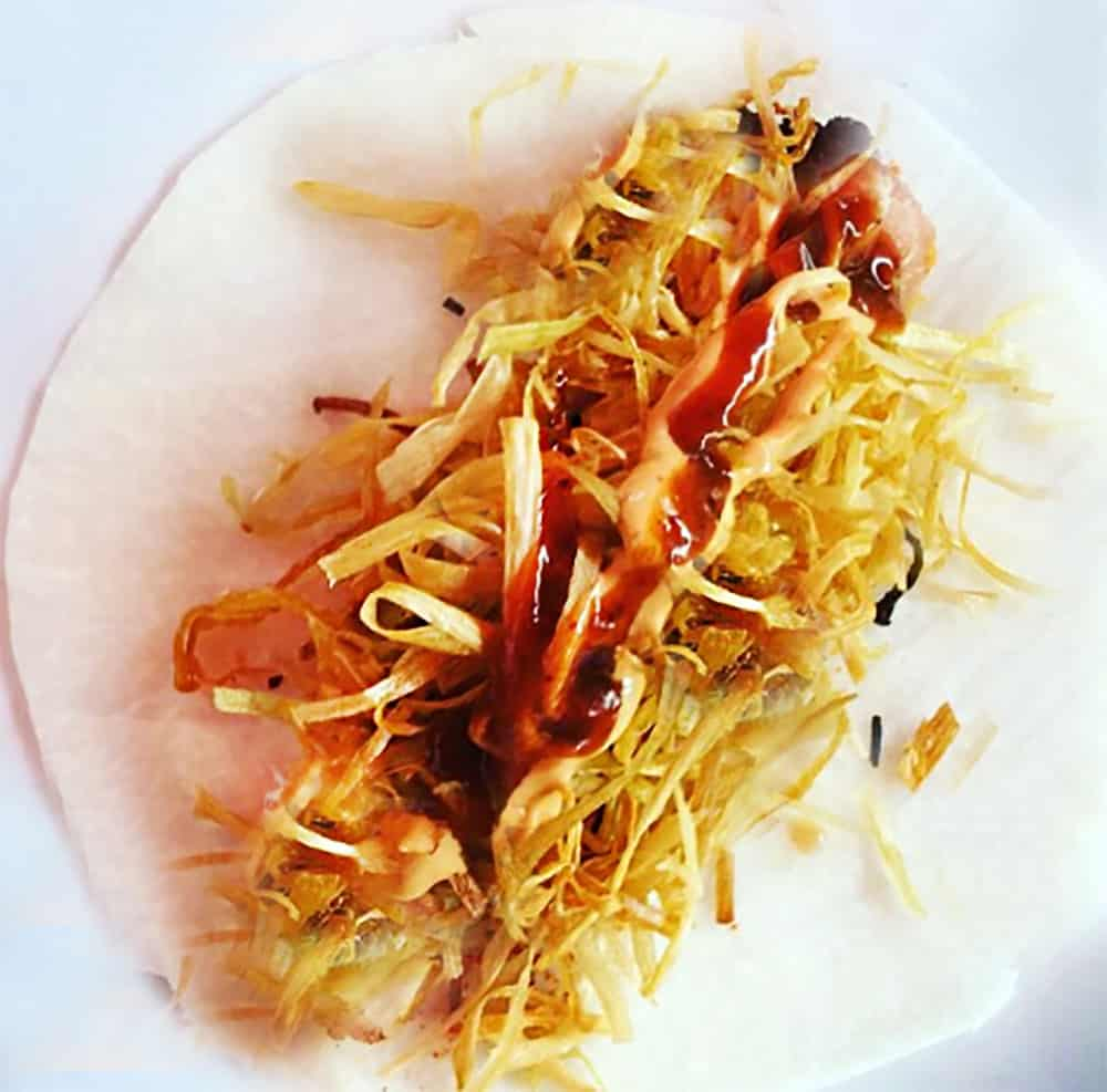 A jicama taco, the signature dish of La Azotea Tapas Bar & Lounge in San Miguel de Allende. It shows the thinly sliced jicama that replaces the tortilla, topped with fried shrimp and crispy frizzled leek.