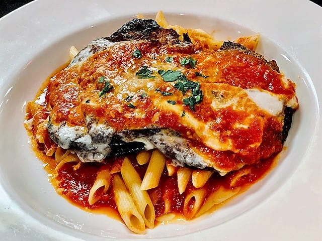 Slices of fried eggplant top pasta and are then smothered with cheese and sauce.