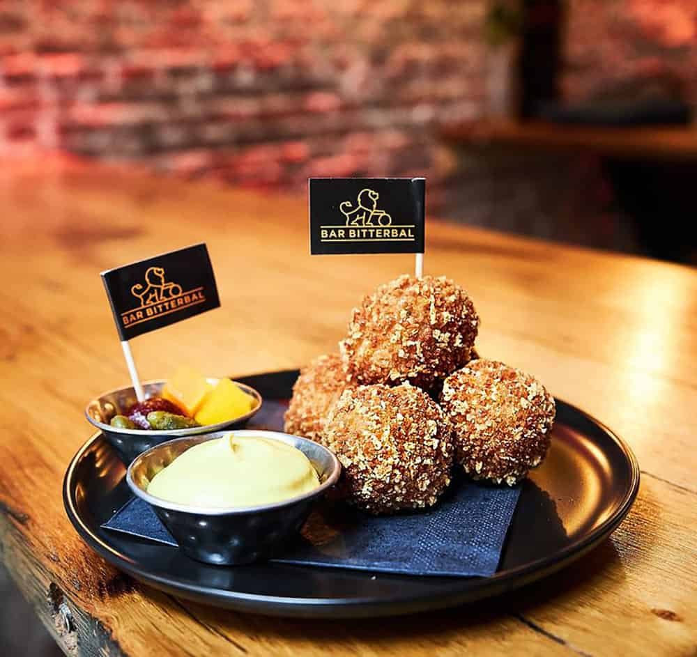 A pile of deep-friend and golden veal bitterballen with dipping sauce and a dish of gherkins at Barb Bitterbal in Amsterdam, where you can sample the largest variety of these popular Dutch bar snacks in the world.